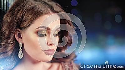 Närbildframsida av örhängen för smycken för charmig kvinnlig modell bärande skinande på neonstrålbakgrund arkivfilmer
