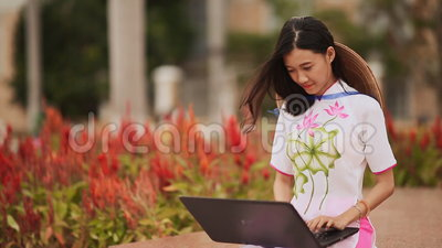 Nätt asiatiskt flickasammanträde med en bärbar dator i parkera i den nationella klänningen Ao Dai med ett lock på baksidan av Non stock video