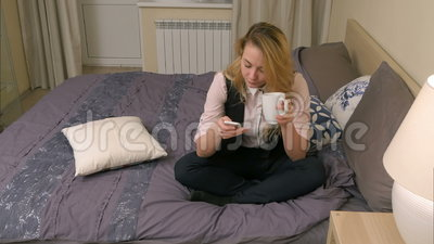 Nätt blond kvinna som bär formellt dräktsammanträde på säng, brukssmartphone och dricker kaffe lager videofilmer