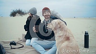 Nätt gift par med dottern och hunden på kull på stranden arkivfilmer