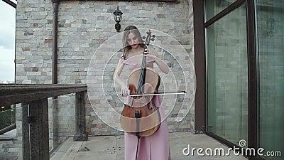 Nätt kvinna som spelar entusiastiskt på violoncellen på balkong lager videofilmer