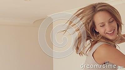 Nätt kvinnabanhoppning på säng lager videofilmer