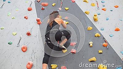Nätt ung idrotts- flickaklättring på en inomhus vagga-klättring vägg arkivfilmer
