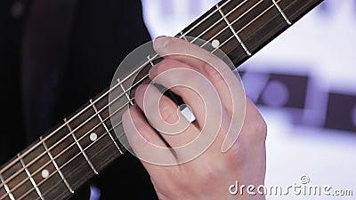 N?rbild av fingrar som organiserar om ackord p? den akustiska gitarren arkivfilmer