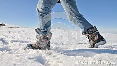 Na de voeten van de mensen in jeans en warme schoenen die in de sneeuw op een de winter zonnige dag lopen Close-up lage hoek kant stock videobeelden
