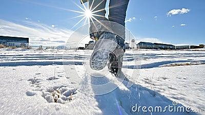 Na de voeten van de mensen in jeans en warme schoenen die in de sneeuw op een de winter zonnige dag lopen Close-up lage hoek rug stock videobeelden