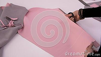 Naaister Cutting Fabric Kleermaker op het werk Het naaien van een sweatshirt van roze stof Workshop voor het maken van kleren, on stock video