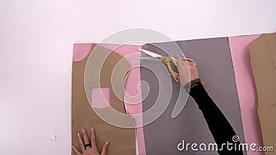 Naaister Cutting Fabric Kleermaker op het werk Het naaien van een sweatshirt van roze stof Workshop voor het maken van kleren, on stock footage