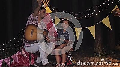 NachtPicnic, Vater und Tochter rufen Mutter beim Picknick beim Abendessen im Wald vor der Kulisse an stock footage