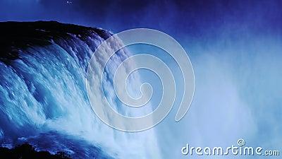 Nachtverlichting bij Niagara-Dalingen De stroom van water wordt verlicht door schijnwerpers van de Canadese kust stock footage