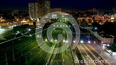 Nachtzicht vanuit de lucht op treinstation, treinen die langzaam van perrons rijden, auto's die op straat rijden, voetgangers die stock video