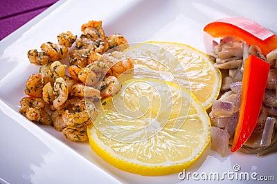 Naczynie z smażącymi krewetkami i cytryną