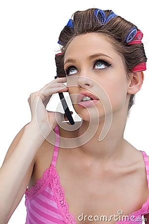 Nadenkend jong model dat haarrollen met telefoon draagt