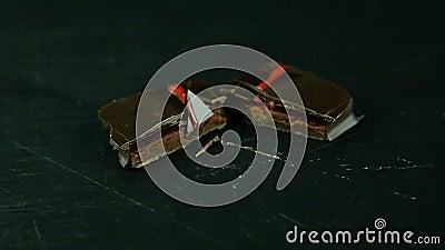 Nadruk binnen bij besnoeiing in half klein vierkant chocoladesuikergoed op keukenlijst stock videobeelden