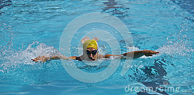 Jeune nageur de garçon dans la piscine, course de papillon