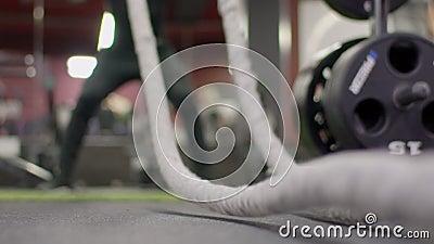 Nahaufnahme des Seils für ein crossfit, mit dem ein Mann in der Turnhalle trainiert stock footage