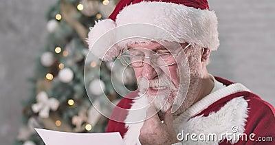 Nahaufnahme des Weihnachtsmanns beim Lesen von Briefsendungen und bei Missverständnissen Senior Mann mit weißem Bart Denken an Ge stock video