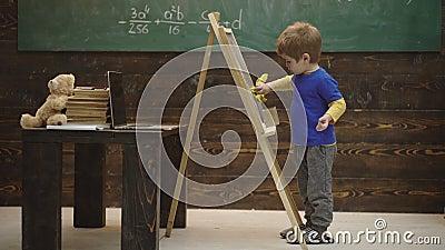 Nahaufnahme eines Jungen, der mit Kreide auf ein Brett schreibt Kleiner K?nstler malt auf einem h?lzernen Hintergrund Konzept der stock video footage