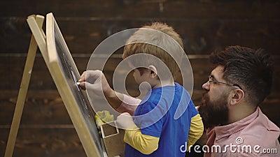 Nahaufnahme eines Jungen und des b?rtigen Mannes, der mit Kreide auf ein Brett schreibt Seitenansichtstudent und Lehrer vor stock footage