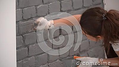 Nahaufnahme eines Mädchens, das eine Backsteinmauer im Grau unter Verwendung des kleinen Pinsels malt stock footage
