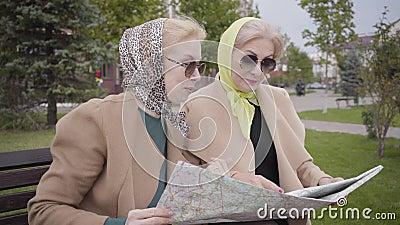 Nahaufnahme zweier reifer Frauen aus Kaukasien in Kopftuch- und Sonnenbrille auf der Bank und Prüfung der Karte Senior stock video footage