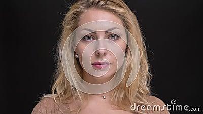 Nahaufnahmeporträt der herrlichen kaukasischen langhaarigen Frau macht und passt ruhig zu Kamera auf schwarzem Hintergrund auf stock video
