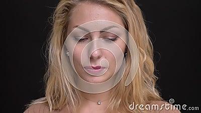 Nahaufnahmeporträt der schüchternen kaukasischen langhaarigen Frau, die ruhig in Kamera auf schwarzem Hintergrund aufpasst stock footage