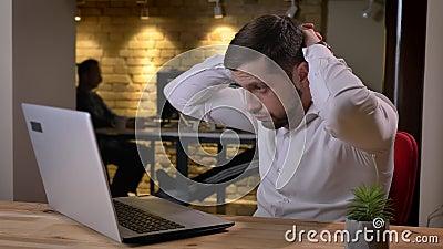 Nahaufnahmeporträt des jungen kaukasischen Geschäftsmannes, der an dem Laptop frustrierend und müde im Büro arbeitet stock video footage