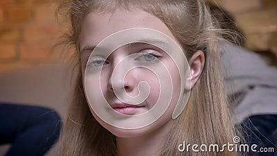 Nahaufnahmeporträt des kleinen hübschen kaukasischen Mädchens, das ihr Haar justiert und ruhig in Kamera im angenehmen Haus aufpa stock footage