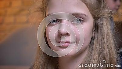 Nahaufnahmeporträt des kleinen hübschen kaukasischen Mädchens, das ruhig in Kamera in der angenehmen Hauptatmosphäre lächelt stock video footage