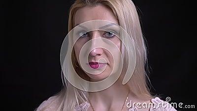 Nahaufnahmetrieb des midddle gealterten Kaukasiers weiblich mit dem blonden Haar, das gerade Kamera mit dem Hintergrund an lokali stock footage