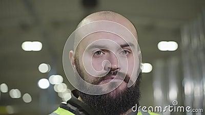 Nahaufportrait eines seriösen, kaukasischen Kopfkaukasiers mit schwarzem Bart, der die Kamera ansieht Angestellter in grüner West stock video