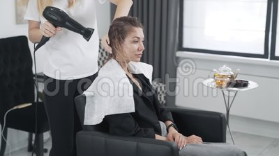 Nahaufwärts, Friseur trocknet Frau nasses Haar mit rundem Kamm, Zeitlupe stock video footage