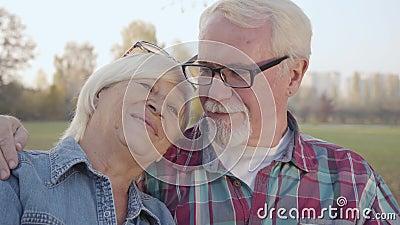 Nahporträt einer glücklichen kaukasisch-pensionierten Familie, die bei Sonnenlicht auf der Bank sitzt und spricht Reife Europäer stock footage