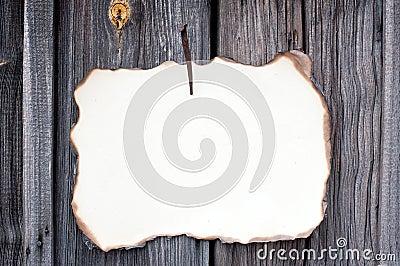 Nailed sheet of paper at wooden wall