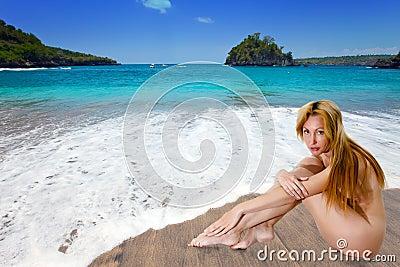 The naked girl on sandy coast at a sea edge.