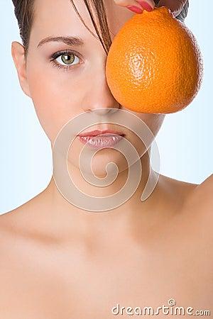 Naranja del asimiento de la muchacha de la belleza de Yung delante del ojo