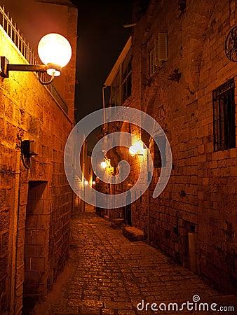 Narrow stone paved medieval street at night