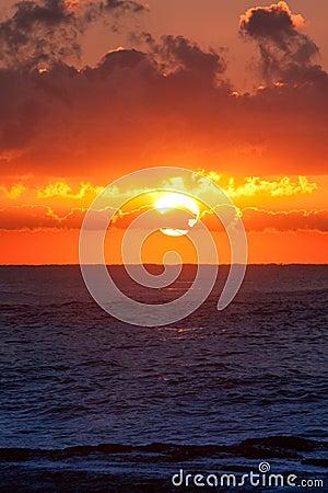Nascer do sol ardente sobre o oceano