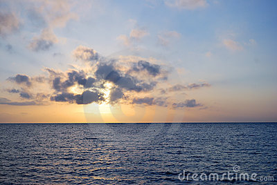 Nascer do sol azul do oceano no tempo nebuloso