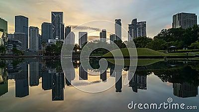 Nascer do sol na skyline da cidade de Kuala Lumpur com reflexão na água vídeos de arquivo