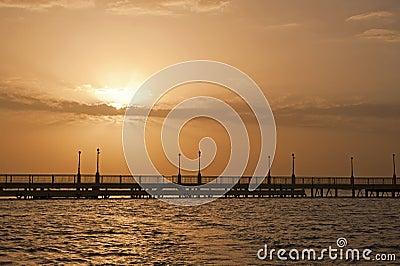 Nascer do sol sobre o oceano em um cais