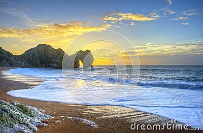 Nascer do sol vibrante sobre o oceano com a pilha da rocha no primeiro plano