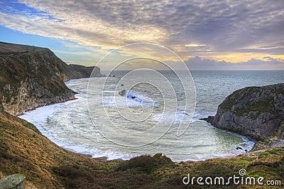 Nascer do sol vibrante sobre o oceano e a angra protegida