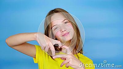 Nastolatka w żółtej koszulce ukazująca kształt serca, uśmiech i patrzenie na kamerę zbiory