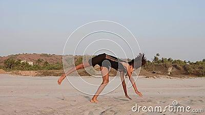 Nastoletnia dziewczyna robi cartwheel dwa czasu i siedzi w dratwie zdjęcie wideo