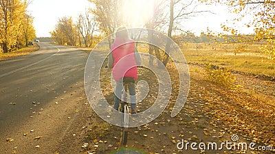 Nastoletnia dziewczyna trzyma ręki na kole i jedzie bicykl na drodze z zatartymi złotymi liśćmi w jesieni zbiory wideo