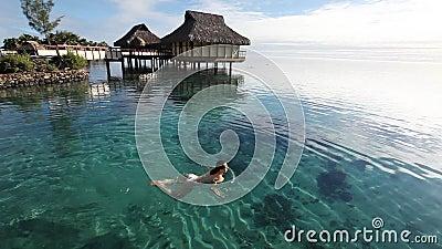 Natação da mulher nova em uma lagoa coral video estoque