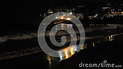 Natthavvågor i ljuset av kuststaden stock video
