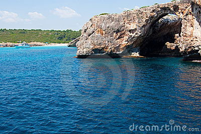 Natural arch and recreational boat at Cala Antena